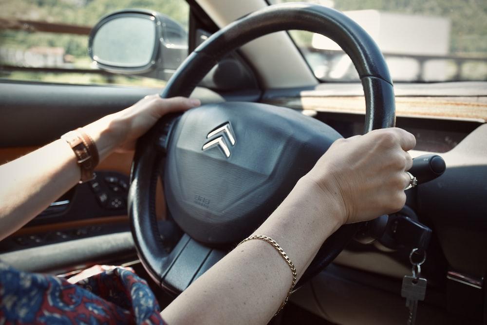 person holding black honda steering wheel