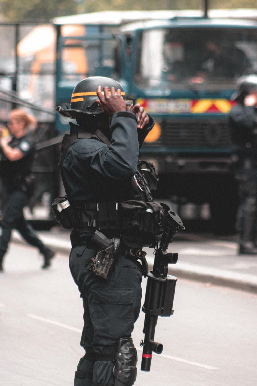 man in black jacket and helmet holding black dslr camera