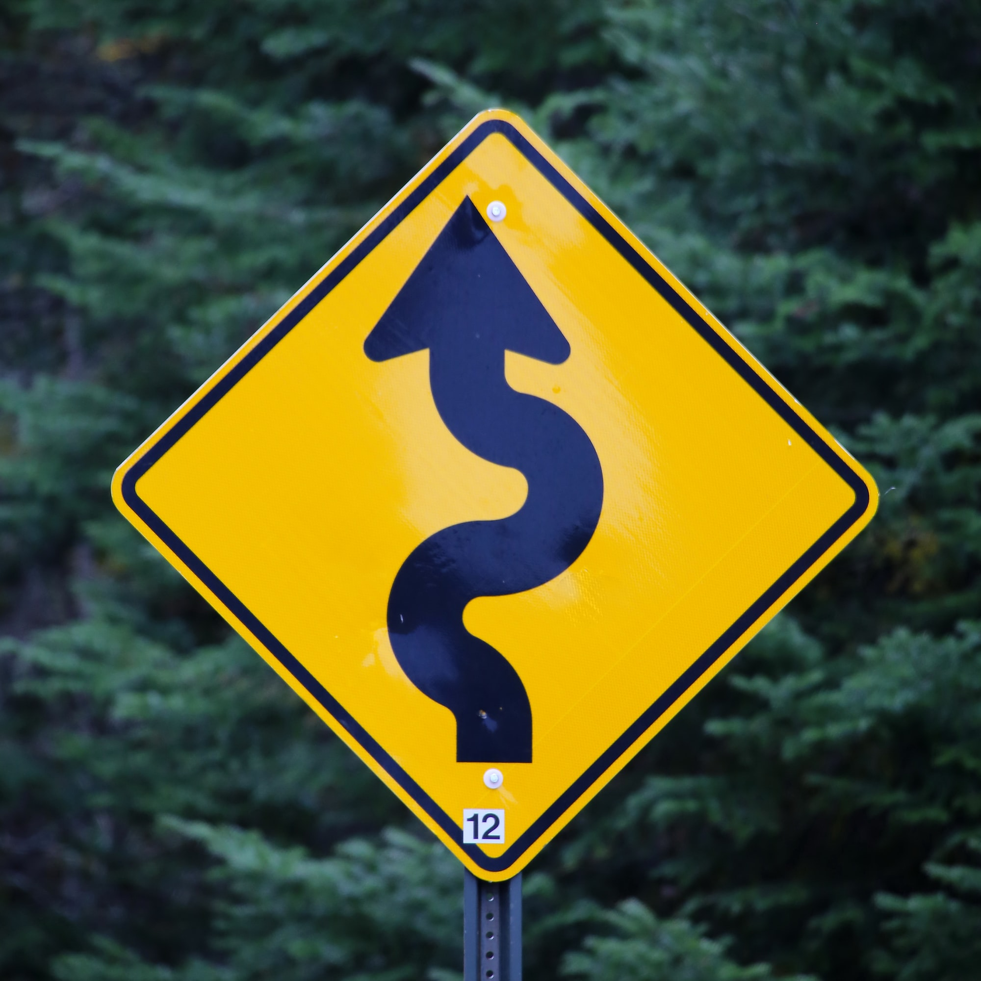 Road sign for curved road ahead.  Storytelling: Could also be used when things are / were not realized in a direct way.