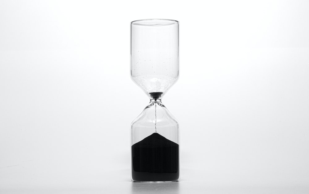 clear glass hour glass with black liquid