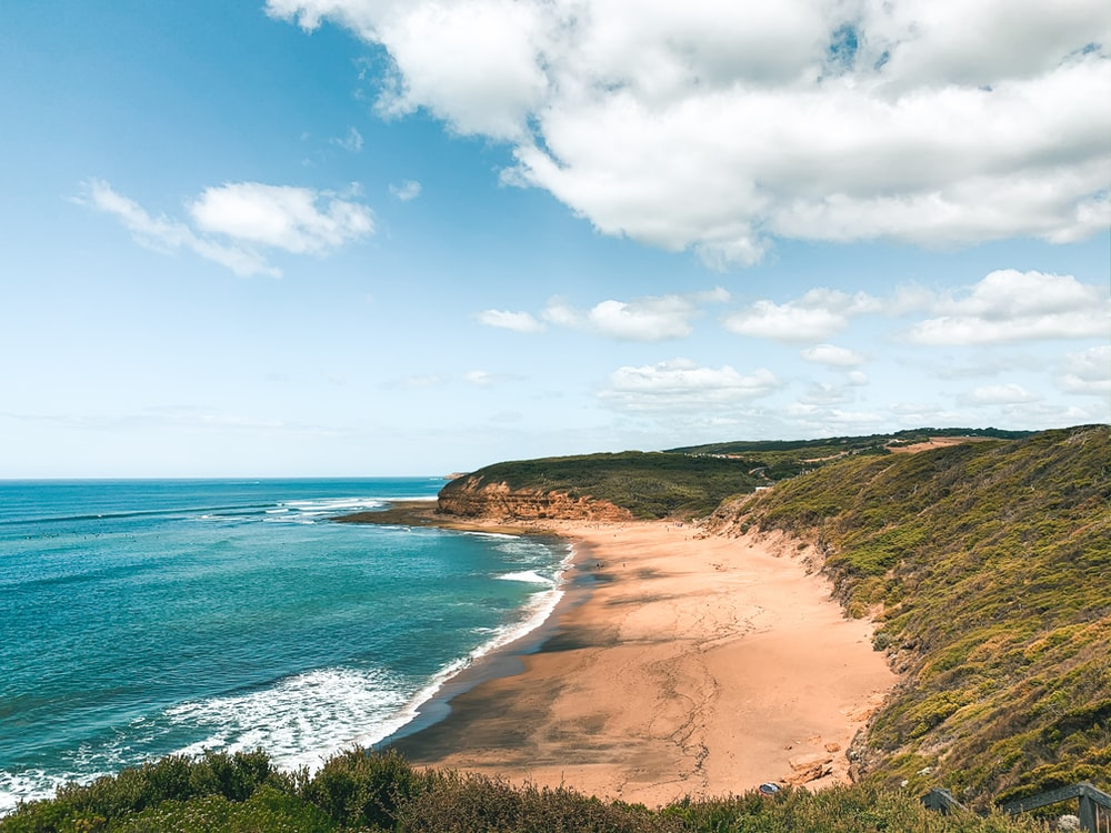 brown sand beach under blue sky and white clouds during daytime