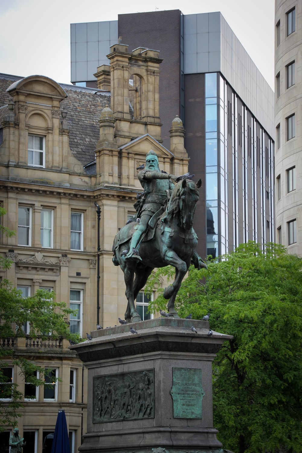 man riding horse statue near brown concrete building during daytime