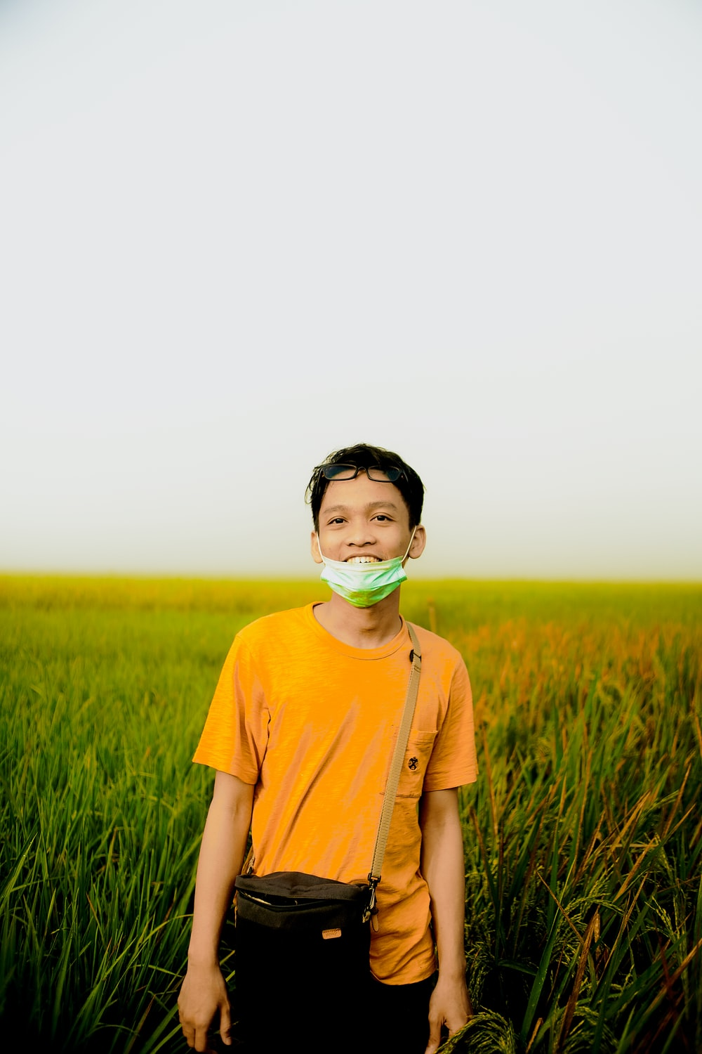 man in blue crew neck t-shirt wearing green mask standing on green grass field during