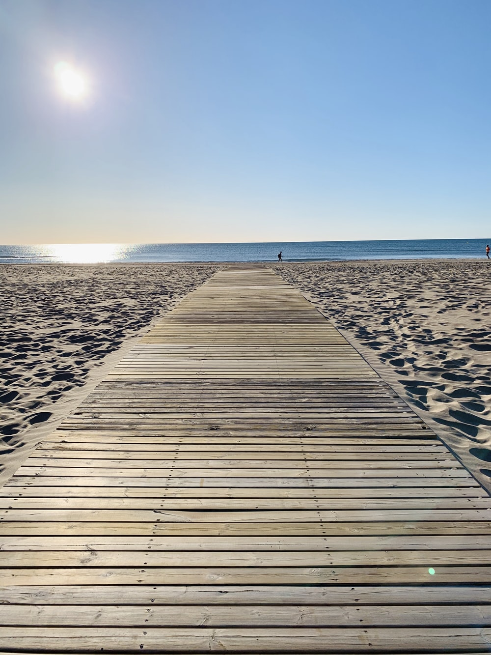 brown wooden dock on beach during daytime