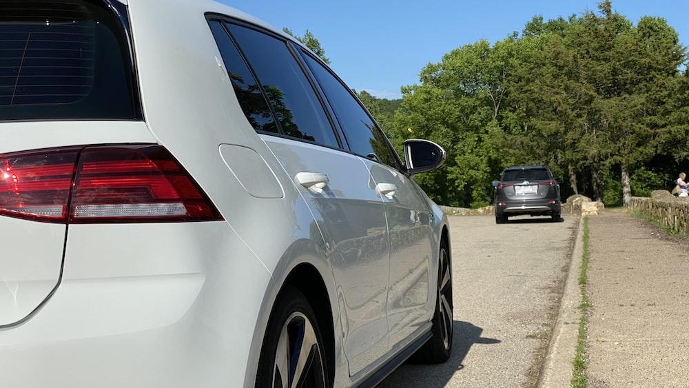 white sedan on gray asphalt road during daytime