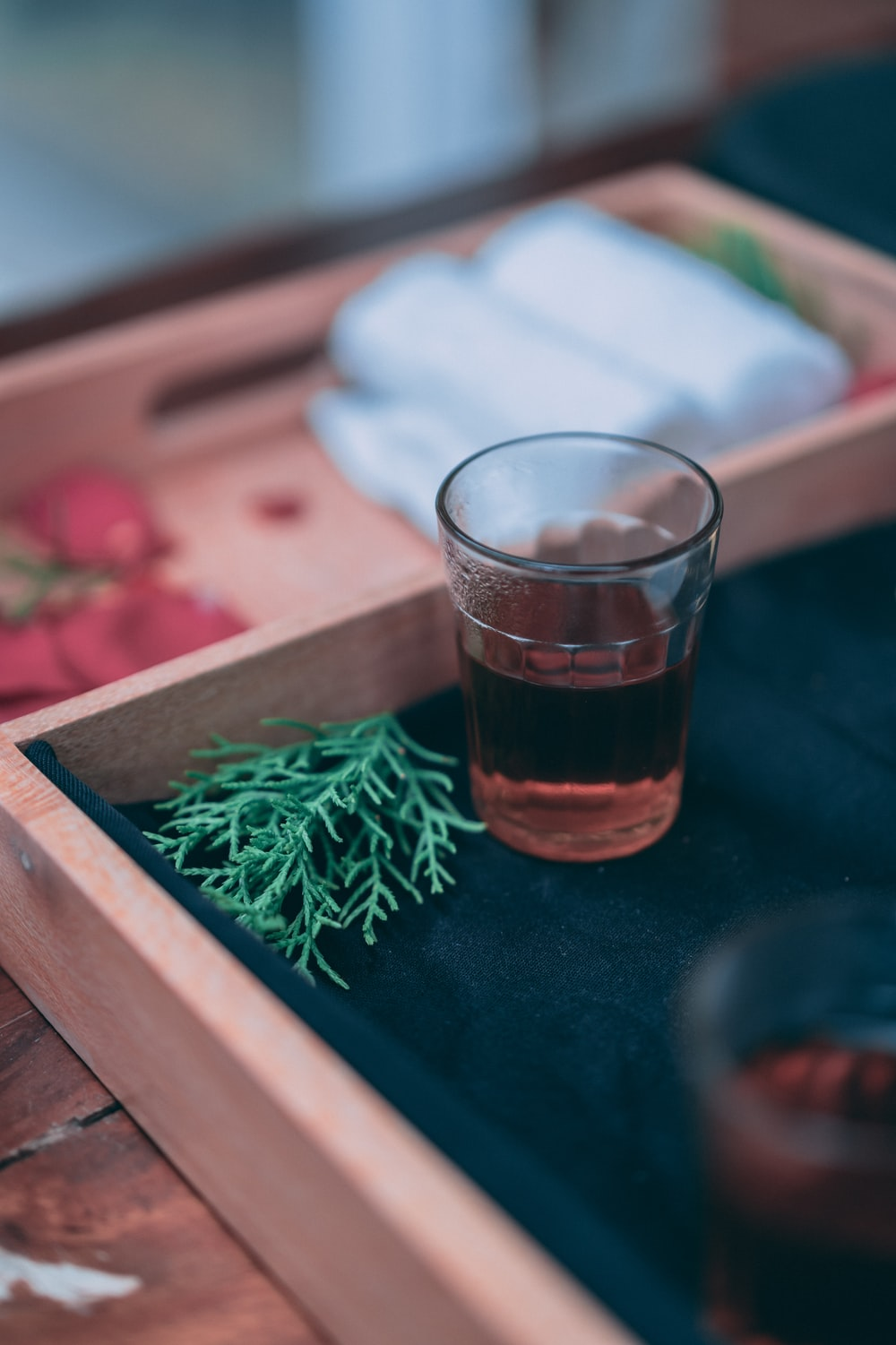 clear drinking glass with brown liquid on brown wooden tray