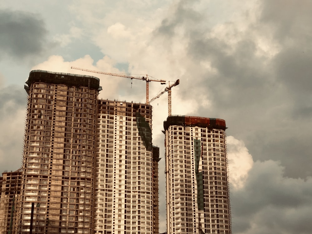 brown high rise building under white clouds during daytime