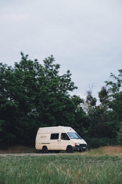 white van parked near green trees during daytime