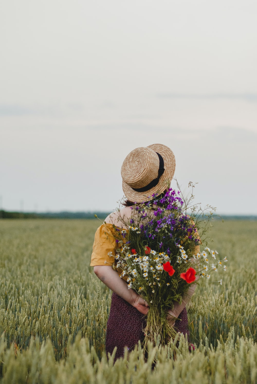 woman in brown sun hat holding red flowers