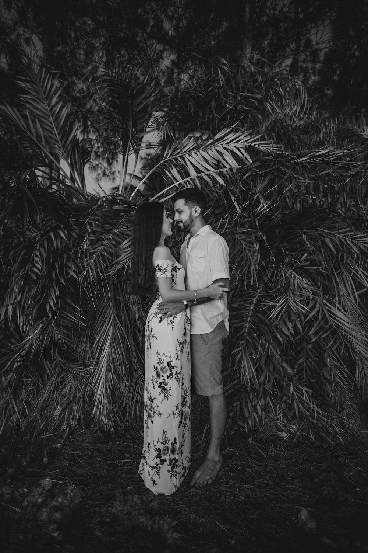 woman in white dress standing near palm tree