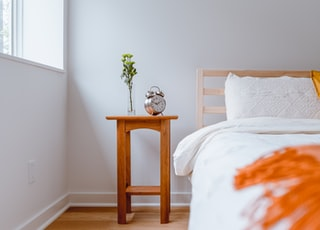 brown wooden table with white and orange floral bed linen