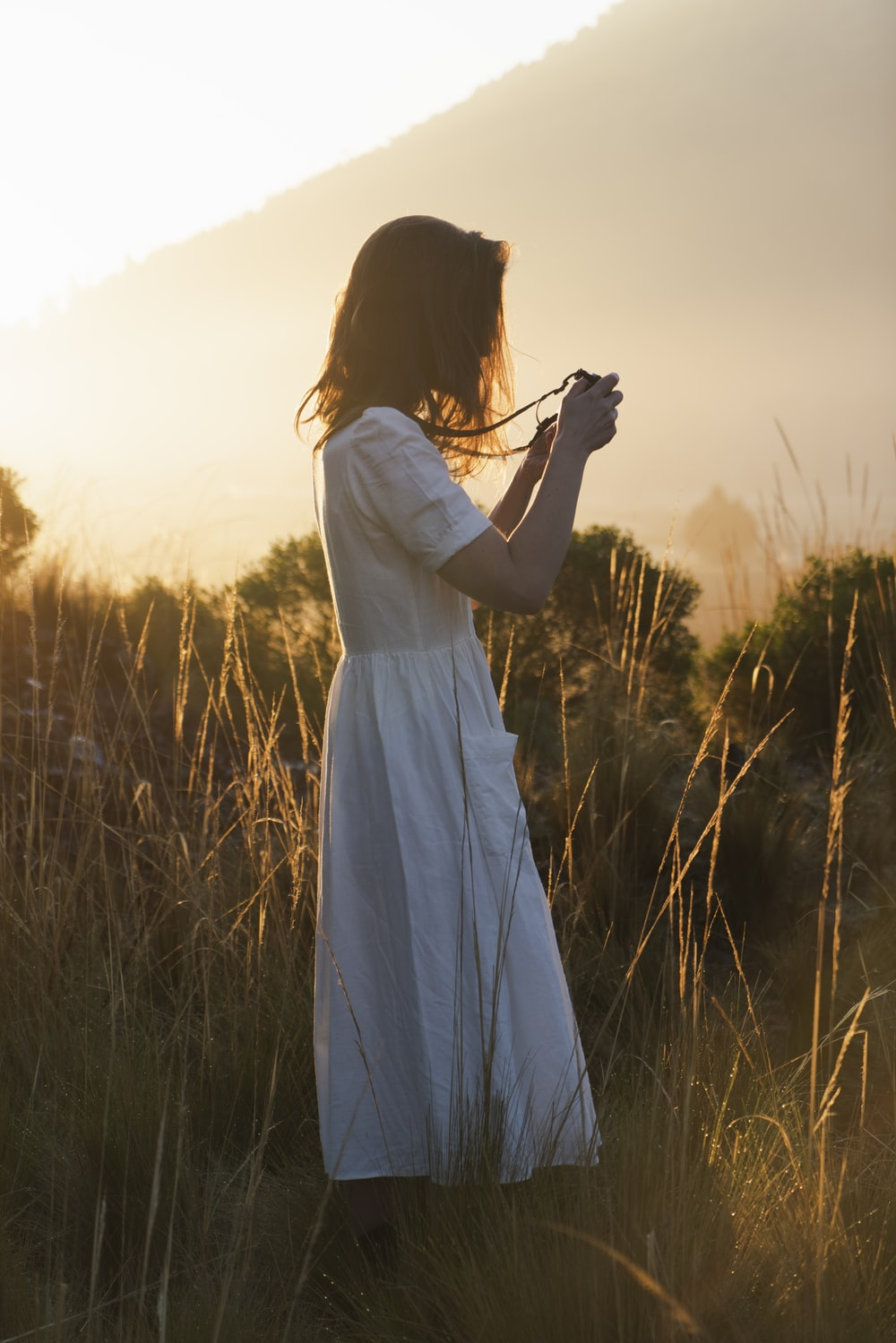 woman in white dress holding camera standing on green grass field during sunset