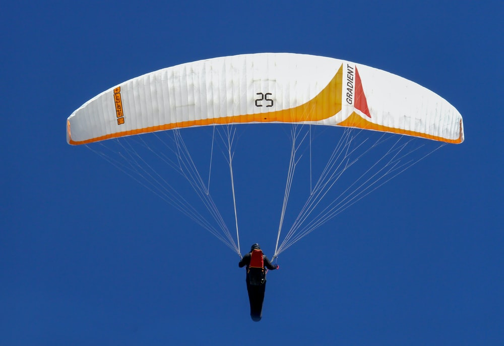 man in black jacket and black pants riding yellow and white parachute