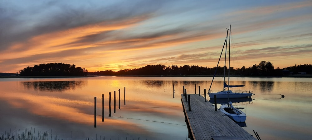 brown wooden dock on calm water during sunset