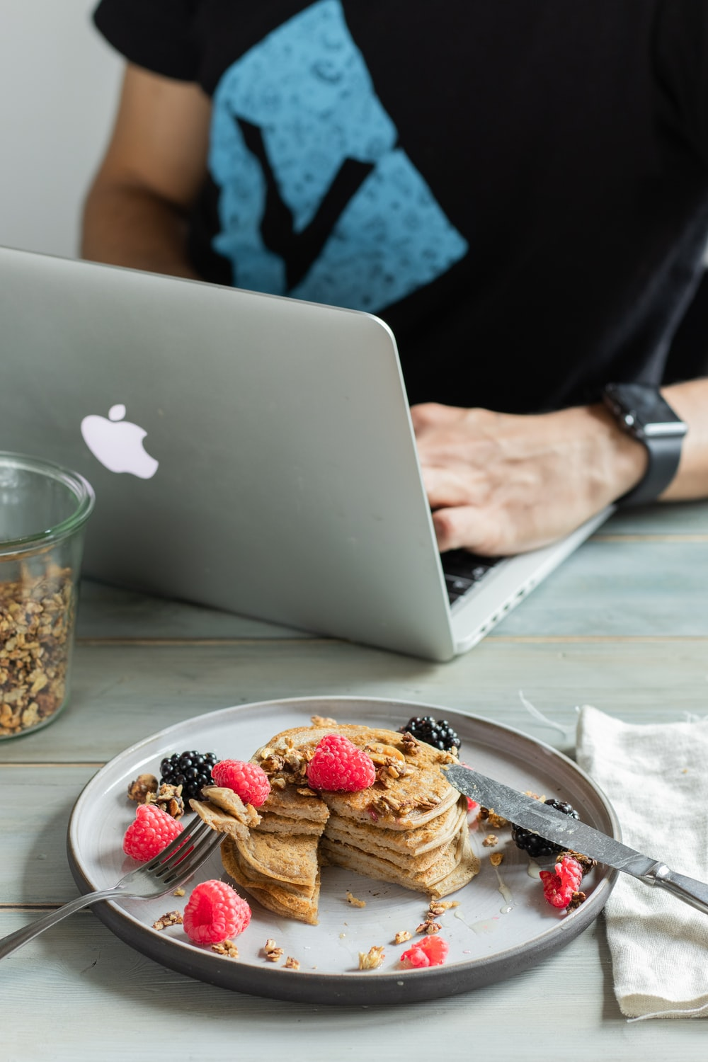 person holding silver macbook near cookies on white ceramic plate