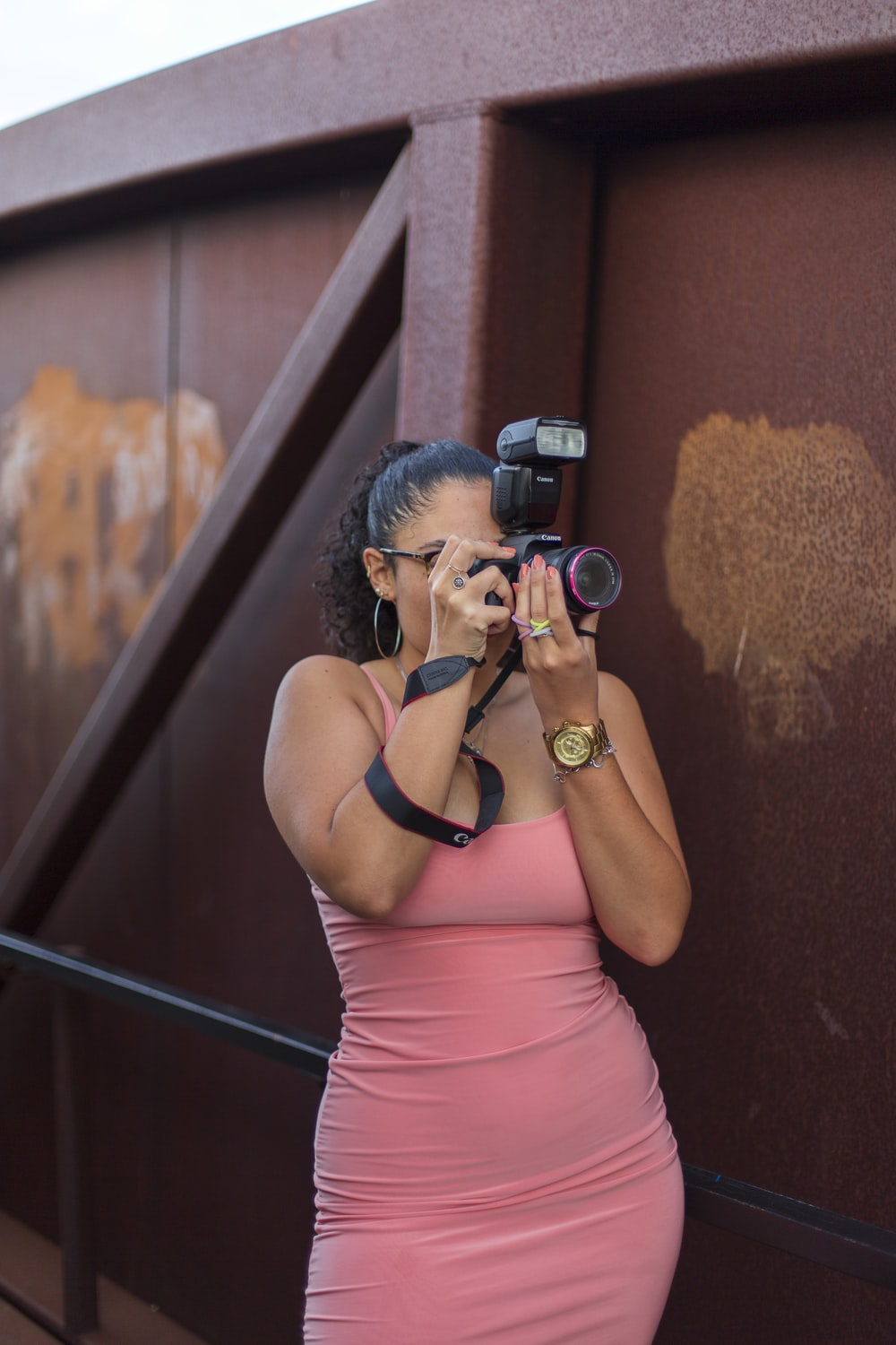 woman in pink tank top holding black dslr camera