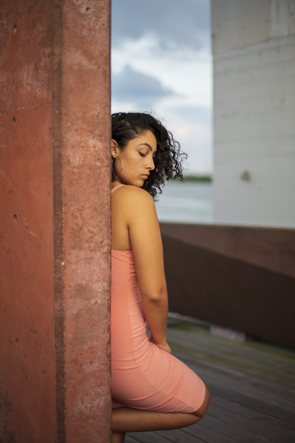 woman in pink tank top leaning on brown concrete wall during daytime