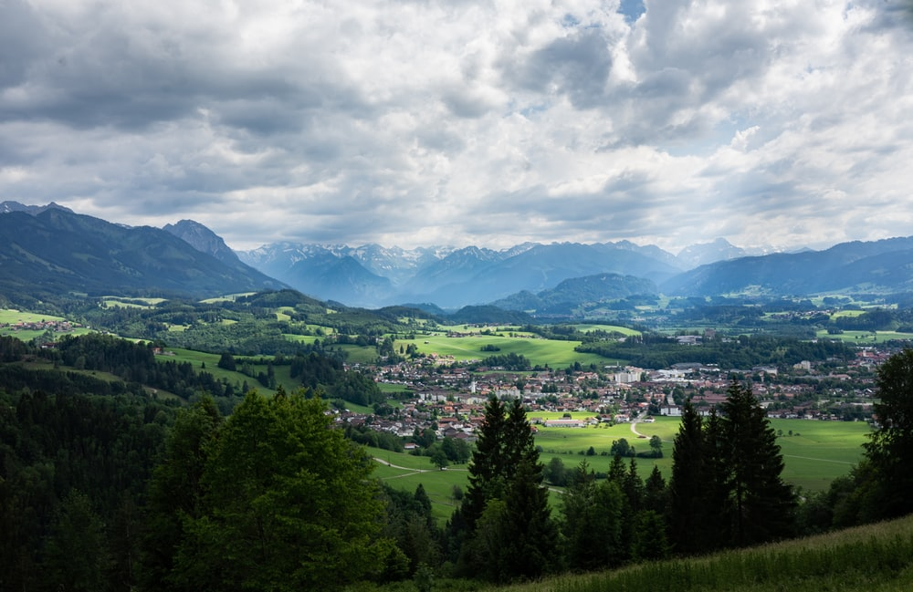 green trees and mountains under white clouds and blue sky during daytime