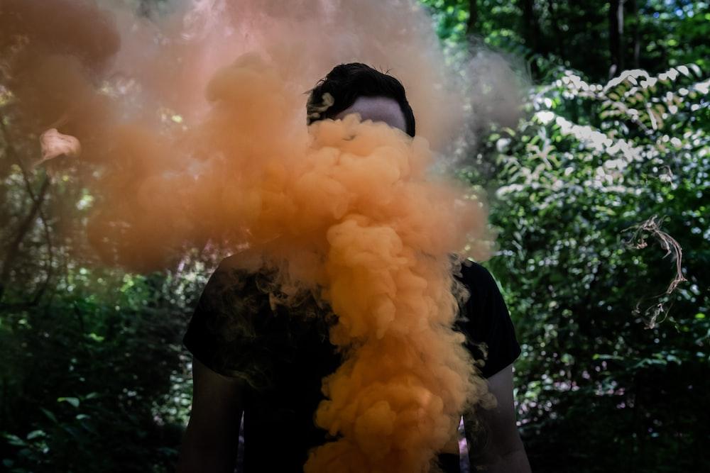 woman in black dress holding white smoke