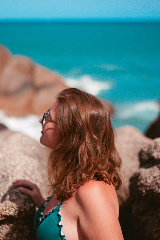woman in black framed sunglasses on white rock during daytime