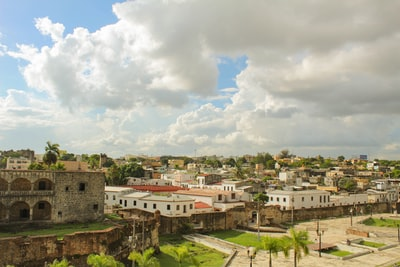 white and brown concrete buildings under white clouds during daytime colonial zoom background