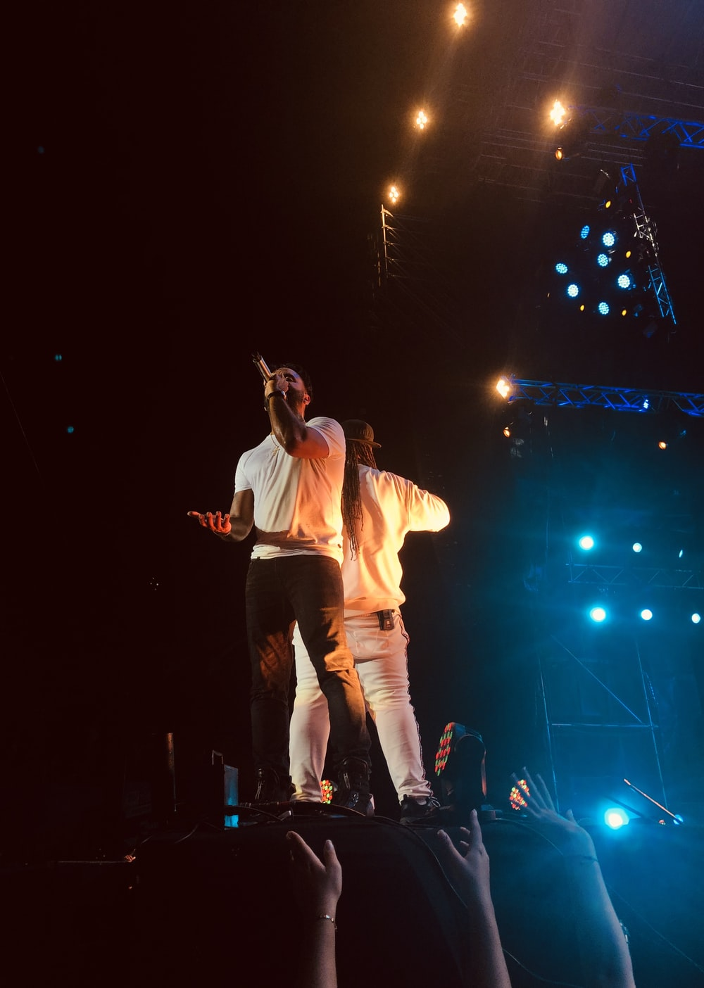 man in white crew neck t-shirt and blue denim jeans singing on stage