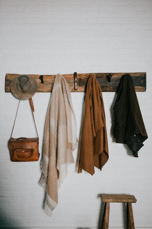brown and beige bath towels hanged on brown wooden hook