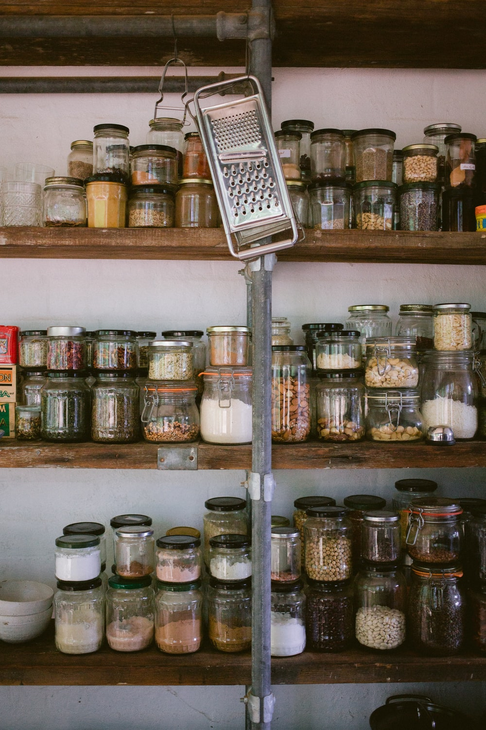 assorted glass jars on white wooden shelf