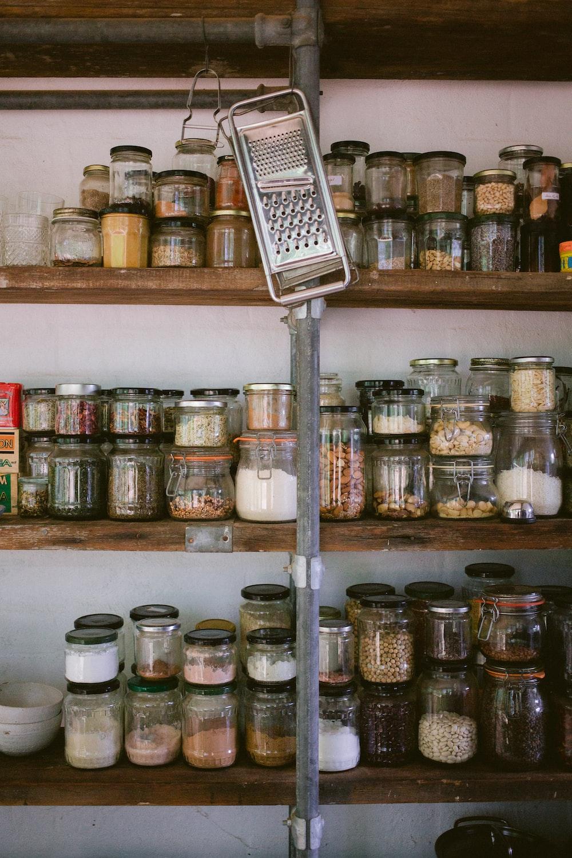 assorted glass jars on white wooden shelf