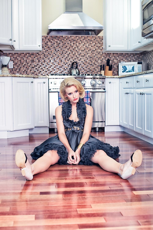 woman in black sleeveless dress sitting on brown wooden floor