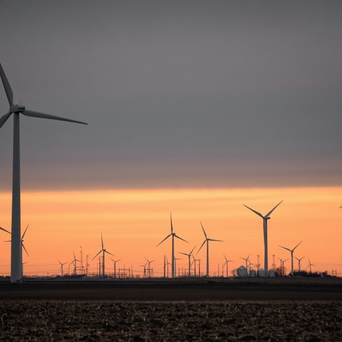 wind turbines on brown field during sunset