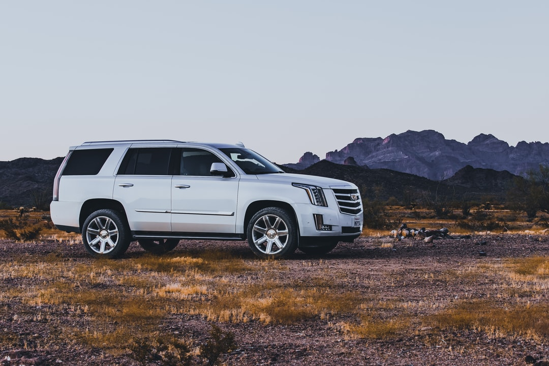 Pearl white Cadillac Escalade at Campsite in the Arizona Desert with mountains in the background.