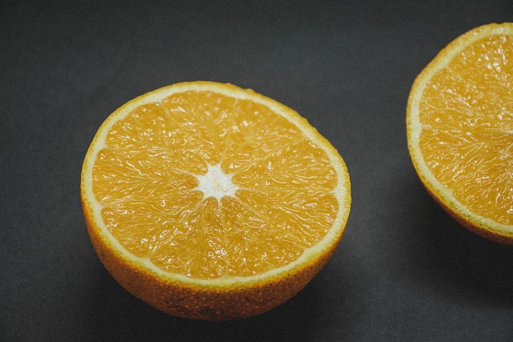sliced orange fruit on black textile