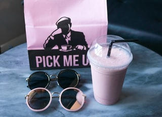 black framed sunglasses beside white disposable cup