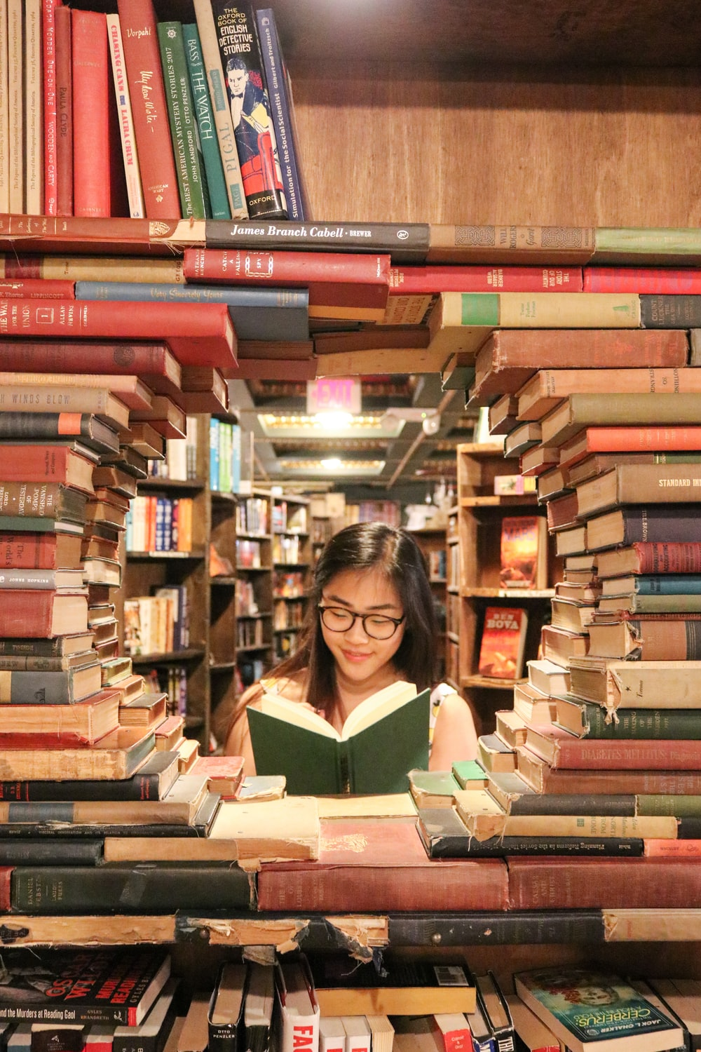 woman in green shirt sitting on books