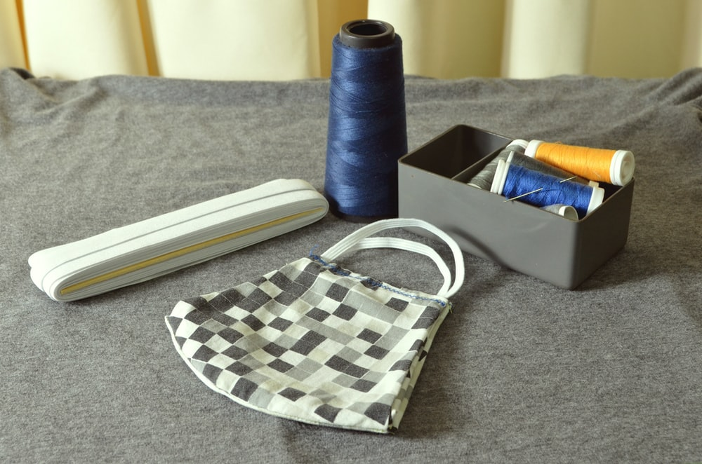 blue thread beside blue and white checkered tote bag