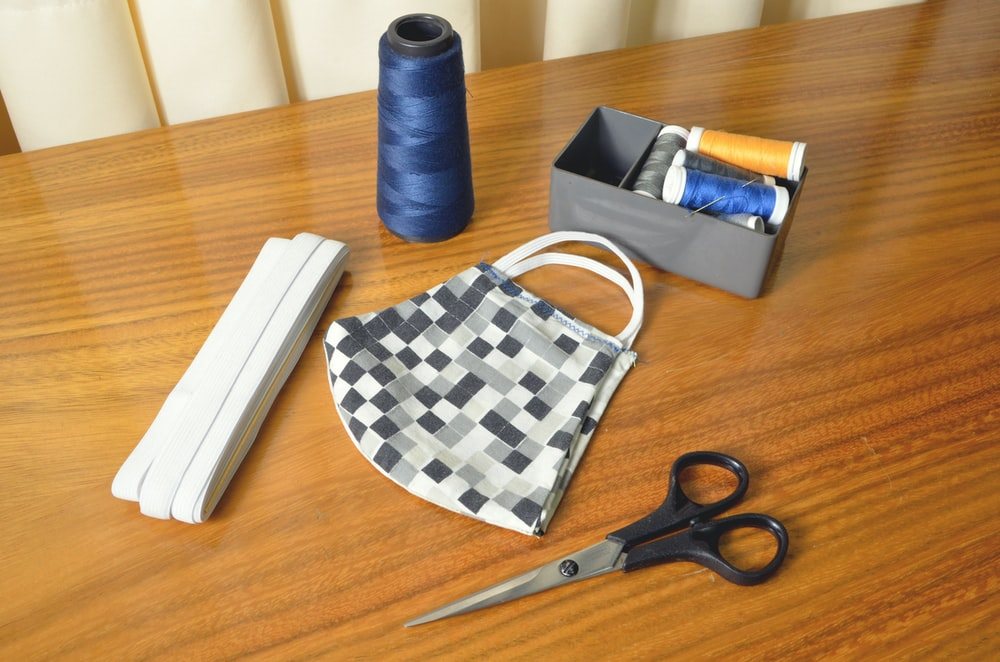black handled scissors beside blue thread and white and black checkered pouch