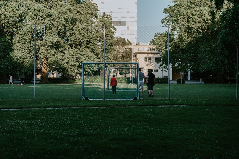 people playing basketball on green grass field during daytime
