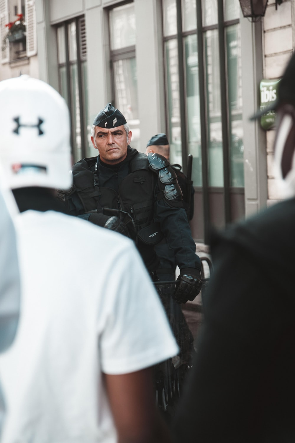 man in black police uniform standing near people during daytime