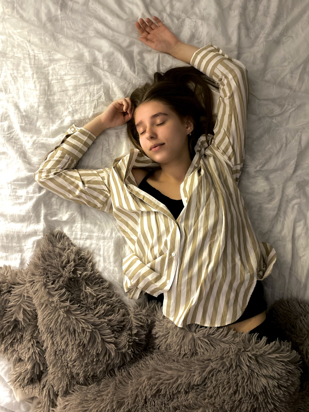 woman in white and black striped long sleeve shirt lying on bed