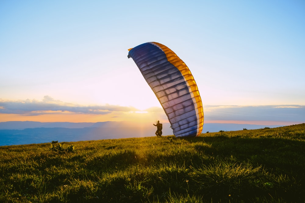 silhouette of person riding parachute during sunset