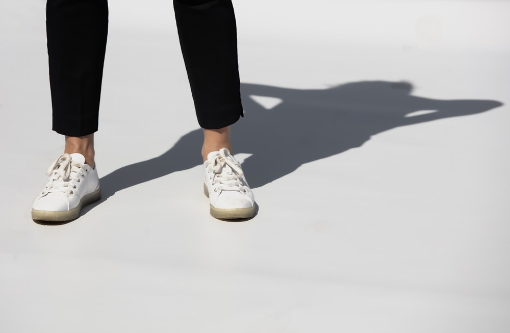 person in black pants and white and brown nike sneakers