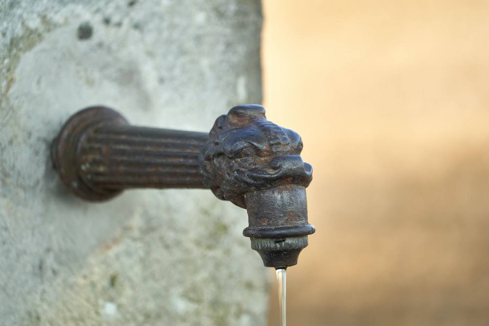 black metal pipe with water droplets
