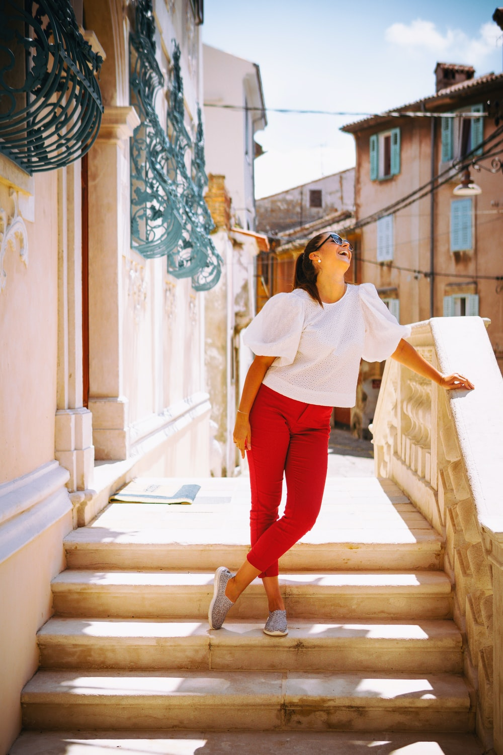 woman in white long sleeve shirt and red pants standing on stairs