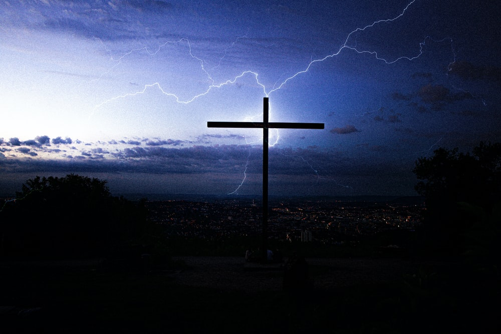 silhouette of cross under cloudy sky during night time