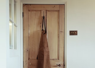 brown coat hanging on door
