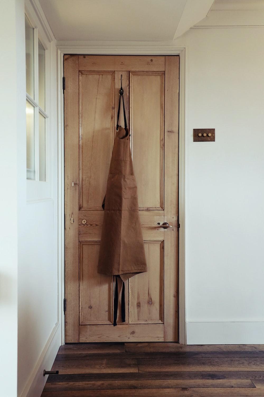 brown coat hanging on door