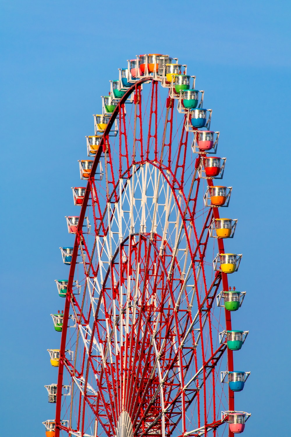 red and yellow ferris wheel under blue sky during daytime