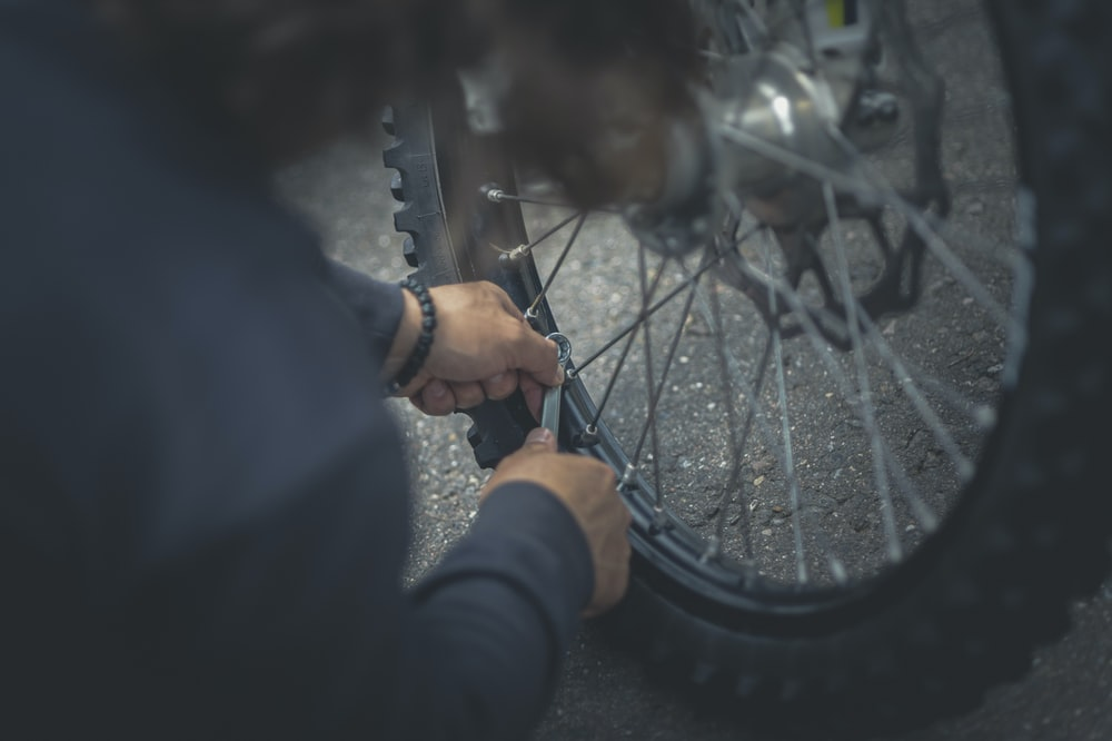 person in black jacket holding bicycle wheel