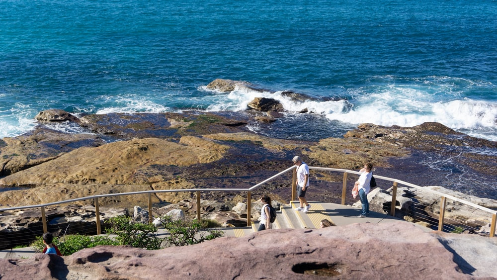 people walking on brown concrete stairs near body of water during daytime